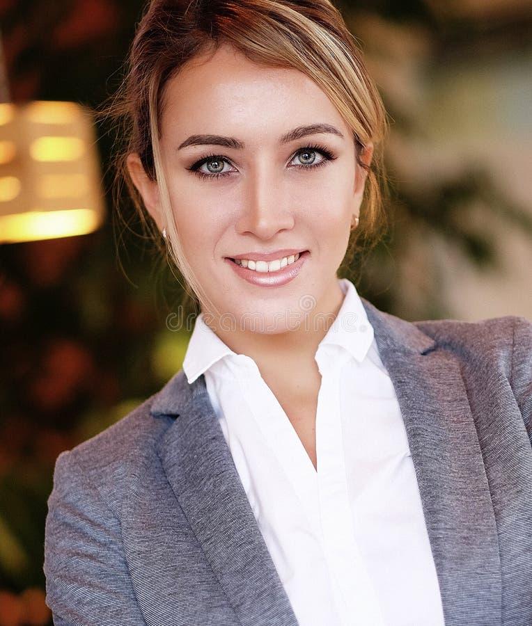 Młody bizneswomanu obsiadanie przy biurkiem i działaniem Uśmiechnięty i patrzejący kamerę fotografia stock