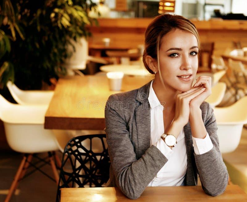 Młody bizneswomanu obsiadanie przy biurkiem i działaniem Uśmiechnięty i patrzejący kamerę Styl życia, ludzie i biznesowy pojęcie, obraz stock