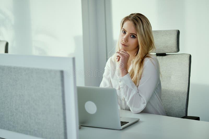 Młody bizneswomanu obsiadanie przy biurkiem z komputerem zdjęcie royalty free