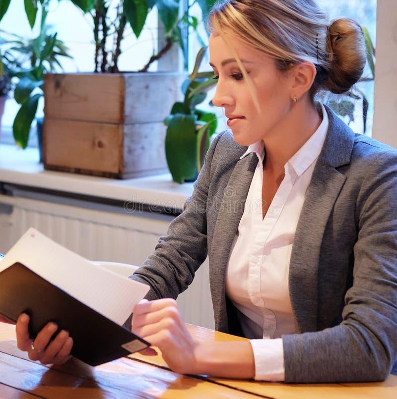 Młody bizneswomanu obsiadanie przy stołem w sklep z kawą i czytaniu zdjęcie stock