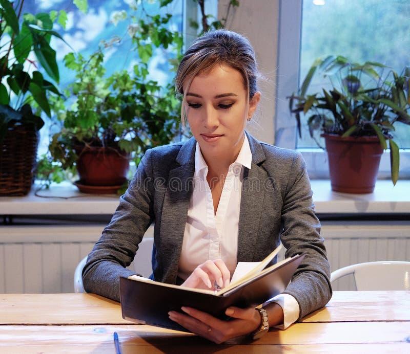 Młody bizneswomanu obsiadanie przy stołem w sklep z kawą i czytaniu obrazy stock
