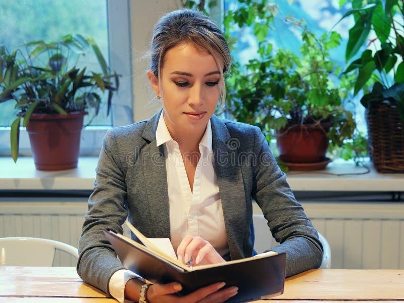 Młody bizneswomanu obsiadanie przy stołem w sklep z kawą i czytaniu obraz stock