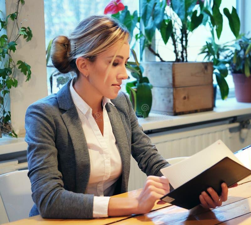 Młody bizneswomanu obsiadanie przy stołem w sklep z kawą i czytaniu zdjęcia stock