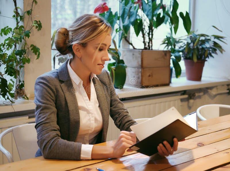 Młody bizneswomanu obsiadanie przy stołem w sklep z kawą i czytelniczej książce zdjęcie royalty free