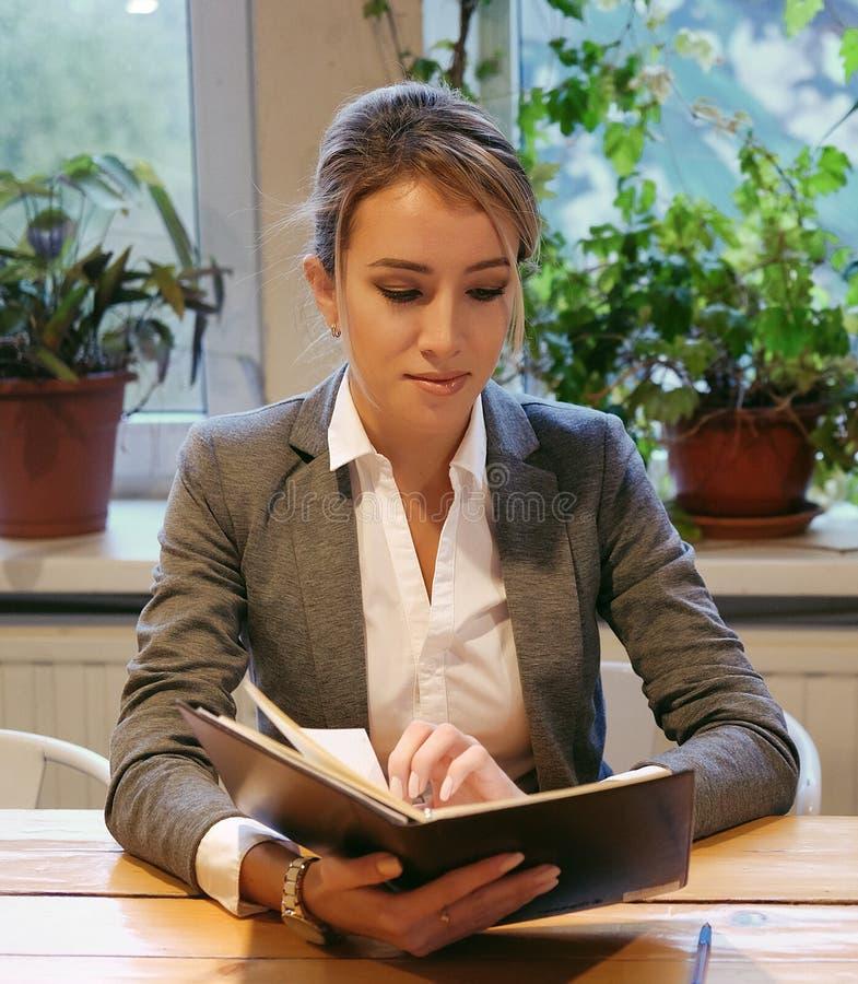 Młody bizneswomanu obsiadanie przy stołem w sklep z kawą i czytelniczej książce obraz royalty free