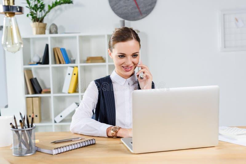 Młody bizneswomanu obsiadanie w biurze przy jej biurkiem pracuje z laptopem i opowiadać obraz stock