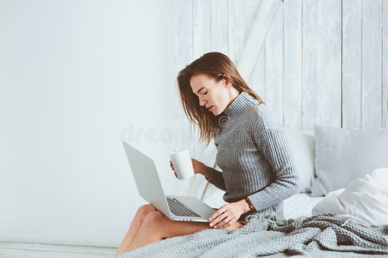 Młody blogger lub biznesowa kobieta pracuje w domu z ogólnospołecznymi środkami, pije kawę w wczesnym poranku w łóżku fotografia stock