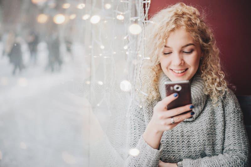 Młody blond kędzierzawy piękny żeński ono uśmiecha się używać smartphone obraz stock