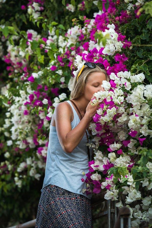 Młody blond kobieta turysta wącha kwiaty w starym grodzkim centrum Alanya obrazy royalty free