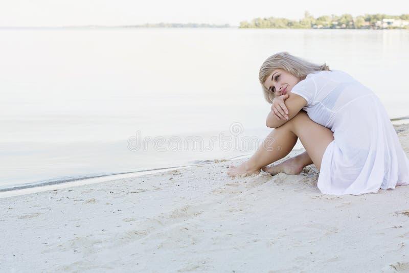 Młody blond kobiety obsiadanie na marzyć i plaży zdjęcie royalty free