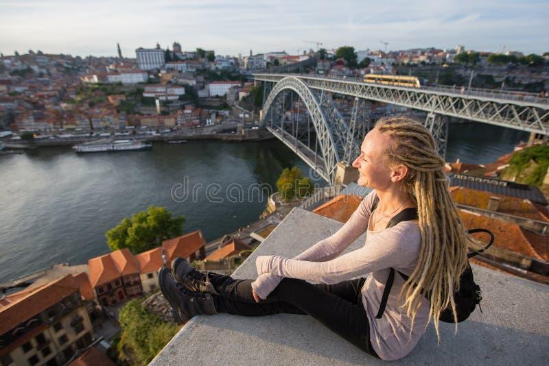 Młody blond kobiety obsiadanie na obserwacja punktu opposite Dom Luis przerzucam most w Porto fotografia stock