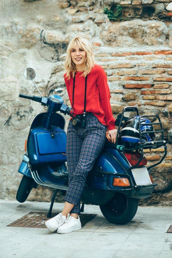Młody blond kobiety obsiadanie na starej błękitnej hulajnodze jest ubranym czerwieni ubrania obrazy stock