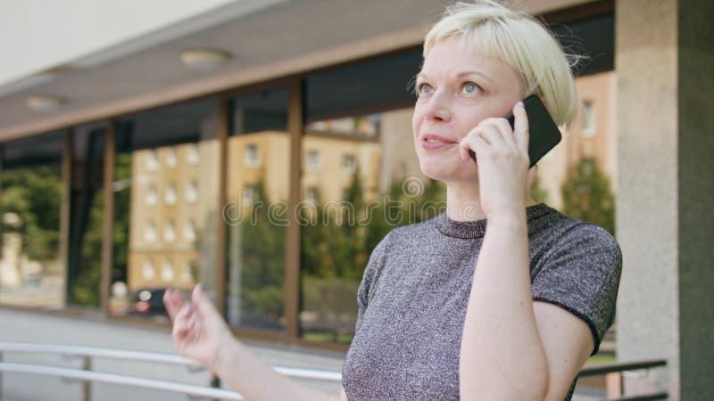 Młody blondynki damy mówienie na telefonie w miasteczku zdjęcie stock