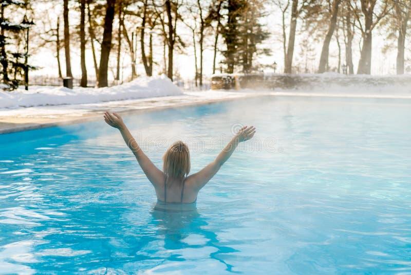 Młody blondynki kobiety dopłynięcie w outdoors basenie przy zimą zdjęcie stock
