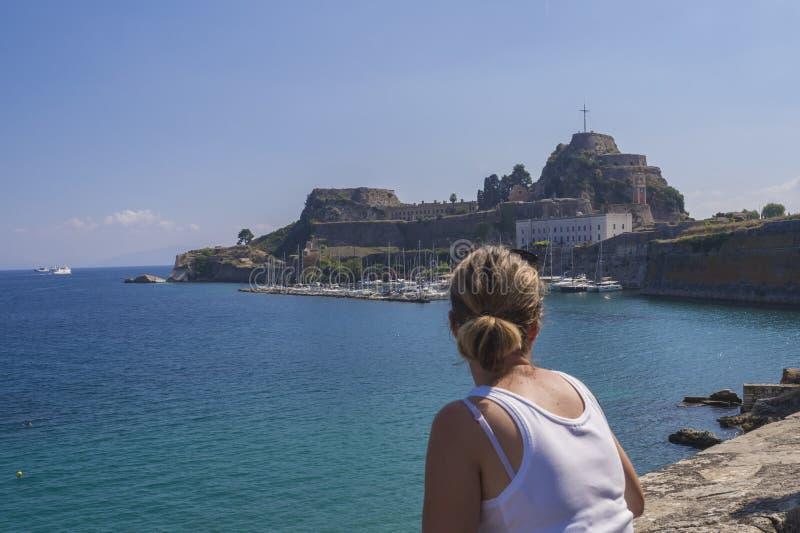 Młody blondynki kobiety dopatrywania widok na Sławnego turystycznego punktu zwrotnego starym venetian fortecy z zegarowy wierza i zdjęcia royalty free