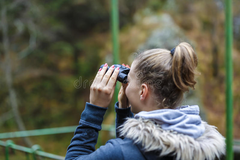 Młody blondynki kobiety turysta patrzeje przez lornetek na falezie zdjęcia stock