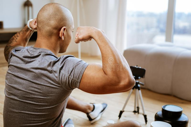 M?ody bodybuilder pokazuje jego ?adnych bicepsy podczas gdy robi? fotografii obrazy stock