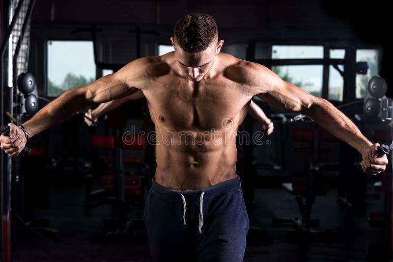 Młody bodybuilder używa sprawności fizycznej wyposażenie fotografia stock