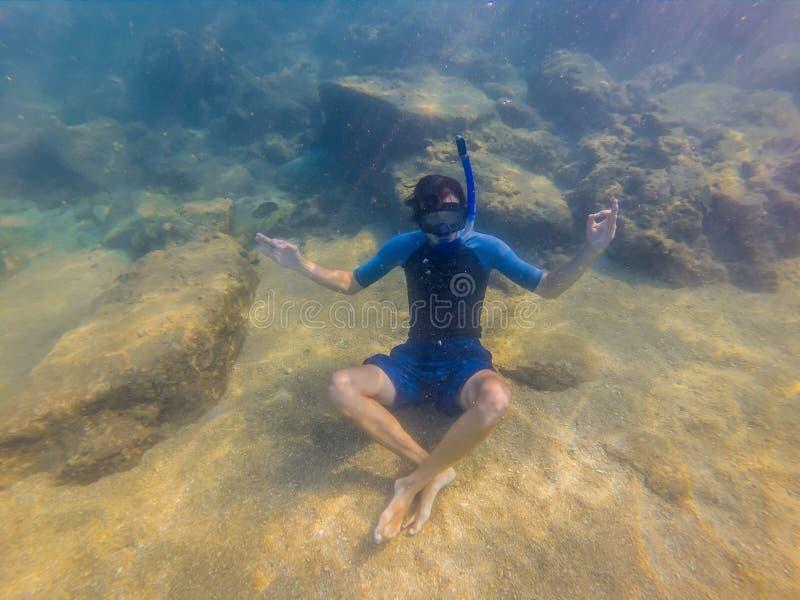 Młody broda mężczyzna z wyposażeniem dla snorkeling w lotosowej pozyci medytuje pod wodą obrazy stock