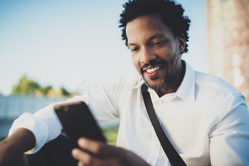 Młody brodaty Afrykański mężczyzna patrzeje smartphone w rękach podczas gdy siedzący przy pogodnym miasto parkiem Pojęcie szczęśl fotografia royalty free