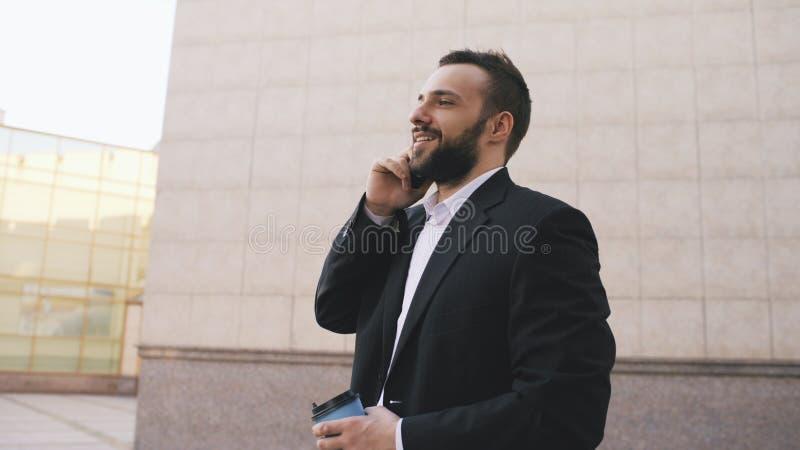 Młody brodaty biznesowy mężczyzna opowiada na telefonie komórkowym robi transakcjom z filiżanką kawy blisko nowożytnych budynków  zdjęcie stock