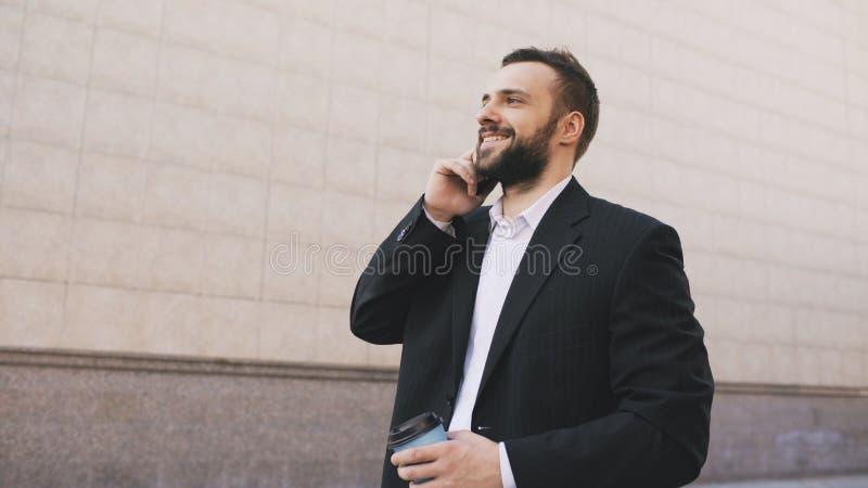 Młody brodaty biznesowy mężczyzna opowiada na telefonie komórkowym robi transakcjom z filiżanką kawy blisko nowożytnych budynków  obraz royalty free