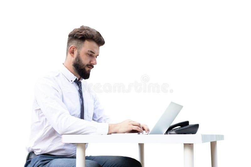 Młody, brodaty facet na stole, za pomocą laptopa, patrzący na ekran mężczyzna pracujący, studiujący lub surfujący po Internecie obraz stock