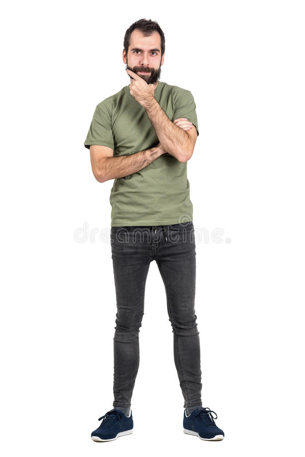 Młody brodaty mężczyzna dotyka jego brodę patrzeje kamerę w zielonej koszulce obraz royalty free