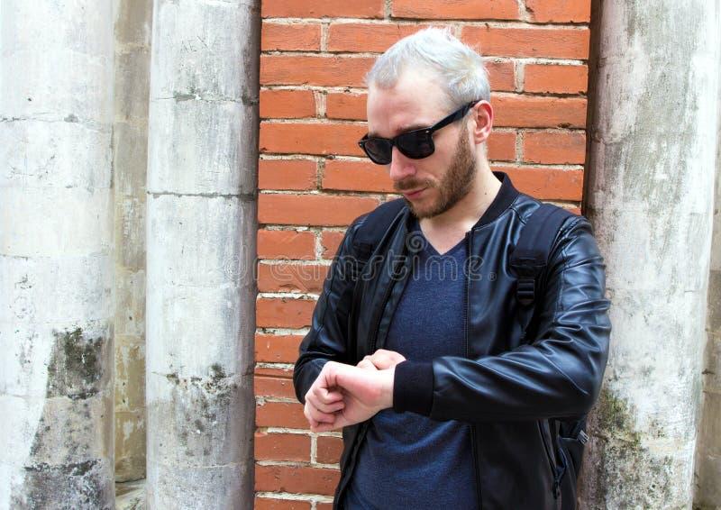 Młody brodaty mężczyzna jest ubranym okulary przeciwsłonecznych i patrzeje na zegarku obrazy stock