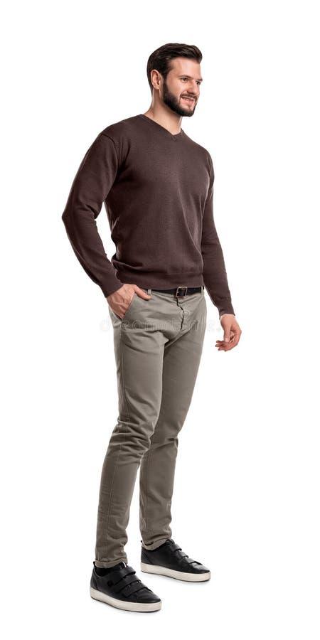 Młody brodaty mężczyzna ono uśmiecha się w przyrodnim zwrocie i chwytach w przypadkowej odzieży stojakach jeden ręka w kieszeni obrazy stock