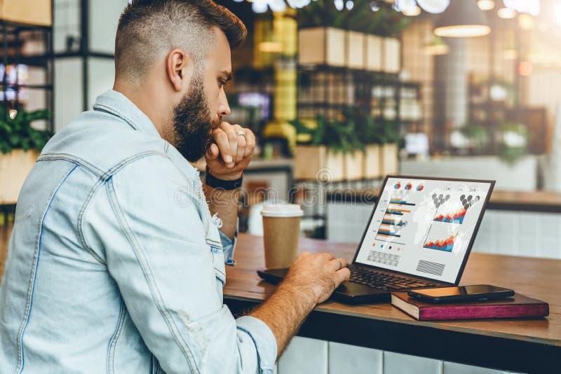 Młody brodaty mężczyzna siedzi w kawiarni, pisać na maszynie na laptopie z mapami, wykresy, diagramy na ekranie Biznesmen pracy w zdjęcie royalty free
