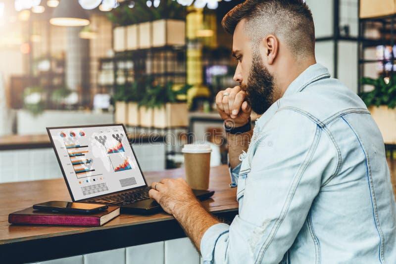 Młody brodaty mężczyzna siedzi w kawiarni, pisać na maszynie na laptopie z mapami, wykresy, diagramy na ekranie Biznesmen pracy w zdjęcia stock