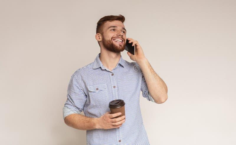 Młody brodaty mężczyzna trzyma filiżanka kawy i opowiada na telefonie zdjęcie royalty free