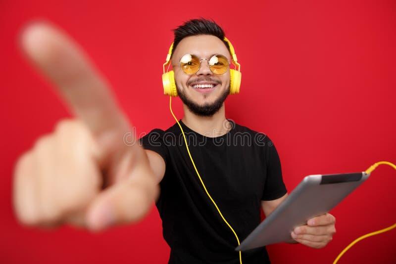 Młody brodaty mężczyzna wskazuje daleko od w żółtych okularach przeciwsłonecznych i hełmofonach pozuje radośnie z pastylką i na c obraz stock