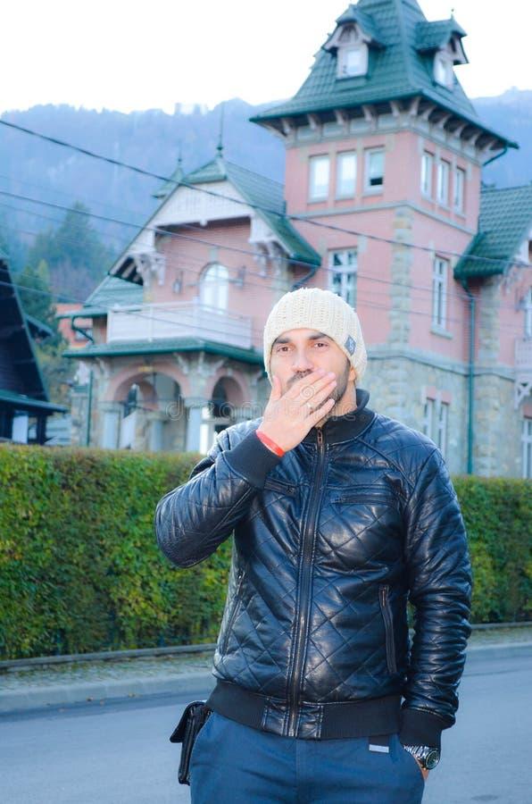 Młody brodaty przystojny mężczyzna z kapeluszu i skóry jacketsending buziakami na tle Piękny stary menchia dom w górze obrazy stock
