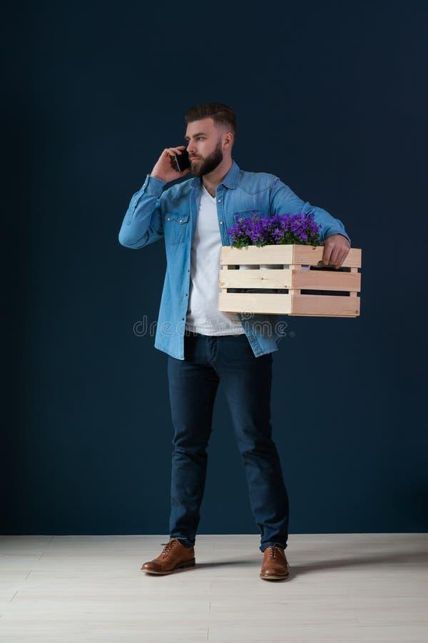 Młody brodaty przystojny męski modniś, ubierający w drelichowej koszula i białej koszulce, stoi indoors trzymać drewnianego pudeł fotografia stock