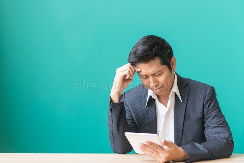 Młody brodaty smutny biznesmen siedzi przy stołem zakrywa jego twarz z jego ręką i trzyma smartphone w jego ręce, zdjęcie royalty free