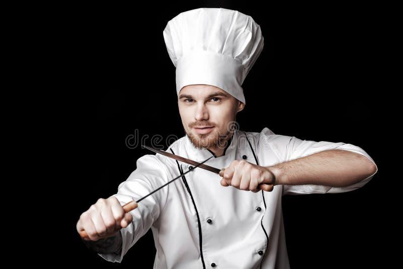 Młody brodaty szef kuchni trzyma dwa noża na czarnym tle w bielu mundurze obraz stock