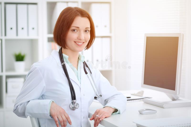 Młody brunetki kobiety lekarki obsiadanie przy stołem i działanie z komputerem przy szpitalnym biurem zdjęcia royalty free