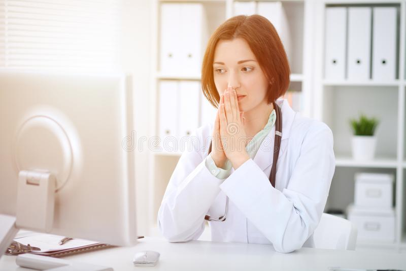 Młody brunetki kobiety lekarki obsiadanie przy stołem i działanie z komputerem przy szpitalnym biurem obrazy royalty free