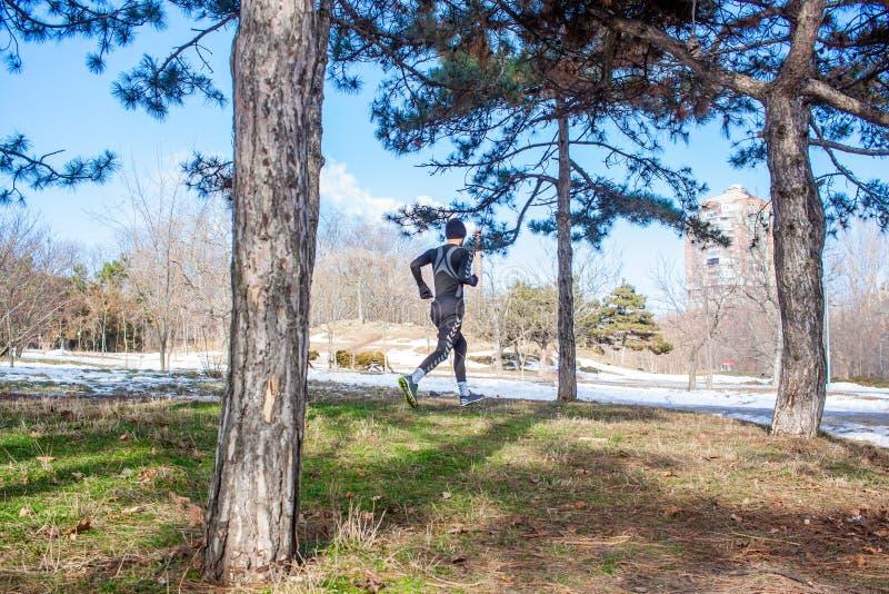Młody caucasian biegacza mężczyzna szkolenie w zima parku fotografia stock