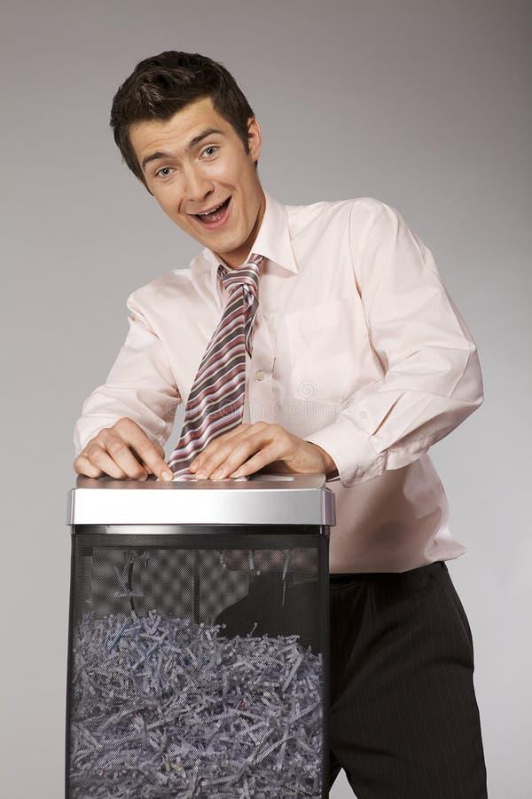 Młody caucasian biznesmen z krawatem łapać w pułapkę w tartej maszynie zdjęcia stock