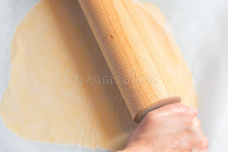 Młody caucasian kobiety kołysanie się z drewnianym wałkowym shortbread ciastem dla Bożenarodzeniowych ciastek między pergaminoweg fotografia stock