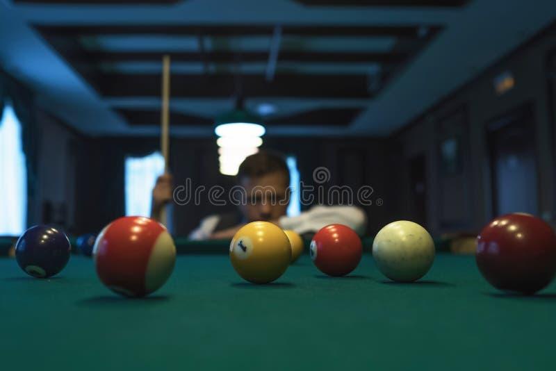 Młody caucasian mężczyzna bawić się billiards przygotowywających strzelać zdjęcie stock