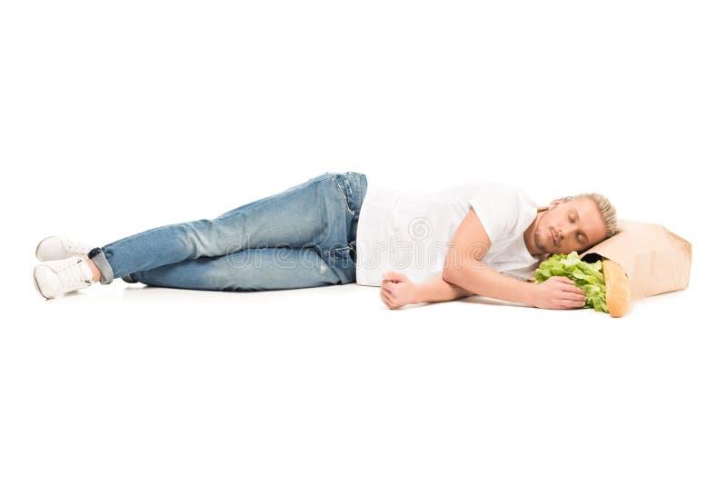 młody caucasian mężczyzna dosypianie na papierowej torbie z jedzeniem obraz stock