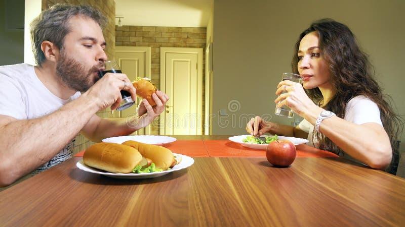 Młody caucasian mężczyzna i kobieta pije miękkiego napój wodę mineralną i Szybkie żarcie versus zdrowy łasowania pojęcie zdjęcia stock
