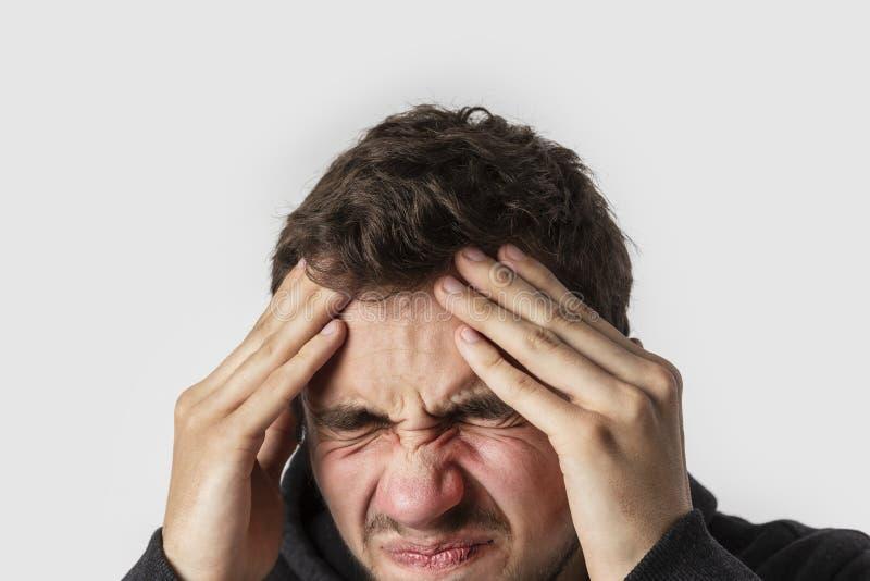 Młody caucasian mężczyzna ma okropne kierownicze obolałość pojedynczy białe tło Migreny pojęcie zdjęcia stock