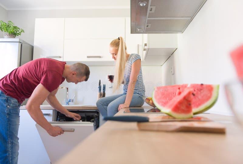 Młody caucasian mężczyzna otwarcia zmywarka do naczyń, podczas gdy jego dziewczyna która siedzi na kuchennym kontuarze, trzyma sz obraz stock