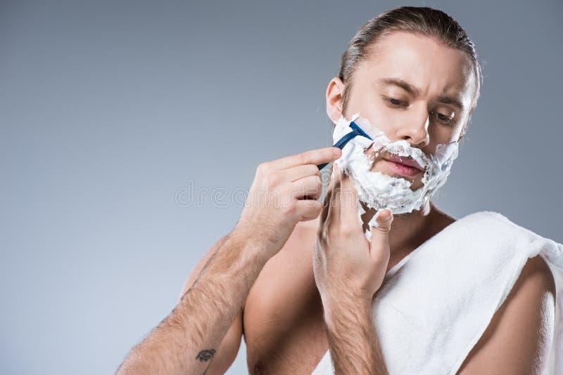 Młody caucasian mężczyzna z golenie pianą na twarzy mienia żyletce w ręce przeciw jego policzkowi, podczas gdy kąpielowy ręcznik  fotografia stock