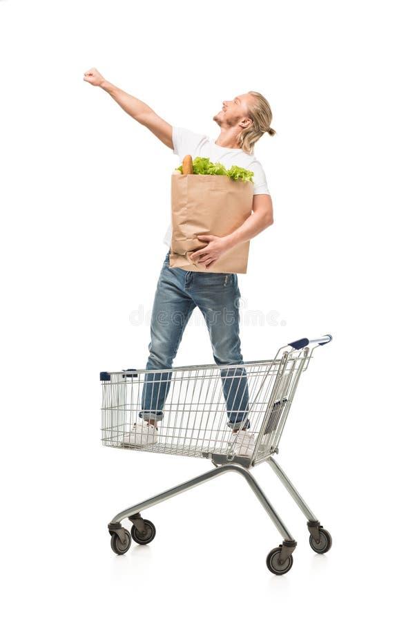 młody caucasian mężczyzna z papierowej torby pozycją w wózek na zakupy zdjęcia royalty free